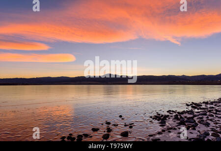 Orange Clouds - Bright orange color sunset clouds rolling over frozen Chatfield Reservoir at foothill of front range of Rocky Mountains. Colorado, USA.