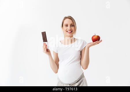 Beautiful pregnant woman holding chocolate bar and red apple isolated over white background - Stock Photo