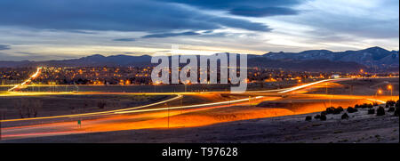 Sunset Highway - A dusk panorama of U.S. Highway 285 winding at foothill of Front Range of Rocky Mountains on a stormy winter evening. Denver, CO, USA. - Stock Photo