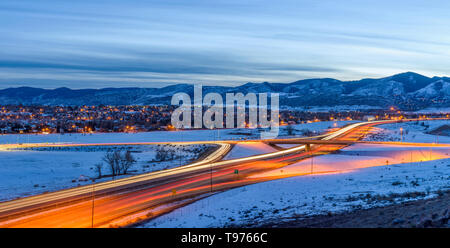Winter Highway - A panoramic overview of U.S. Highway 285 winding at foothill of Front Range of Rocky Mountains on a stormy winter evening. Denver, CO. - Stock Photo