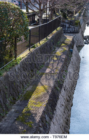 Shadow of a metal fence on a stonewall above the Lake Biwa Canal, Okazaki Enshojicho, Sakyo-ku, Kyoto, Honshu, Japan - Stock Photo