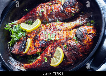 delicious freshly fried dorado fish with lemon slices in a  black ceramic baking dish on a concrete table with a kitchen towel and parsley, view from  - Stock Photo