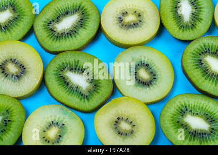 selection of slices of yellow and green kiwi fruit on a bright high contrast turquoise background