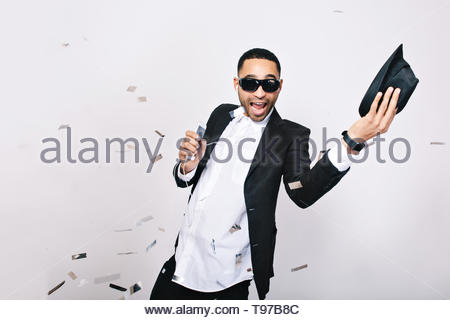 Funny excited young man in suit having great party celebration time in tinsels on white background. Wearing black sunglasses, smiling, singing, listening to music, expressing positivity - Stock Photo