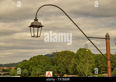 Turin, Piedmont, Italy. May 2019. The Basilica of Superga filmed by Piazza Vittorio. The green hills and a lamppost in the foreground are the setting - Stock Photo
