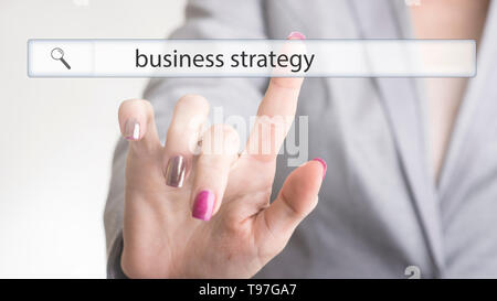 Female hand touching a website navigation bar with the text business strategy on a transparent virtual screen. - Stock Photo
