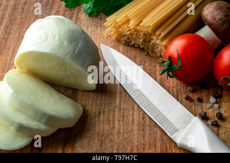 on a wooden board lay mozzarella sliced next to her knife on the right side sea salt with red and black pepper, above cherry tomatoes, mushrooms, raw  - Stock Photo