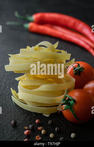 on black background balls of raw fettuccine pasta with fresh tomatoes with roots, black and red peppercorns and two pods of chili - Stock Photo