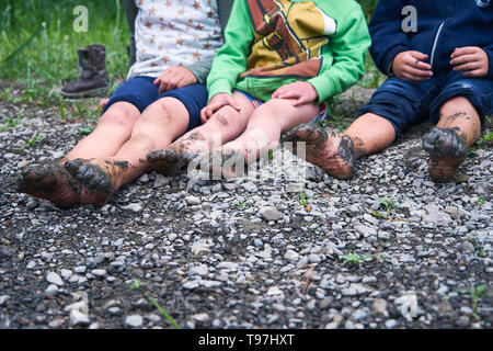 three-kids-with-bare-and-muddy-feet-sit-