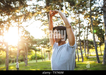 Confident young asian athlete man wearing sportswear doing exercises outdoors at the park - Stock Photo