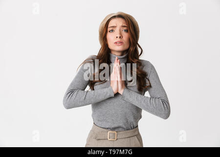 Photo of focused woman 30s wearing hat keeping palm together for pray isolated over white background - Stock Photo