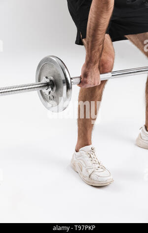 Cropped image of a young sports fitness man isolate over white wall background make exercises with barbell. - Stock Photo