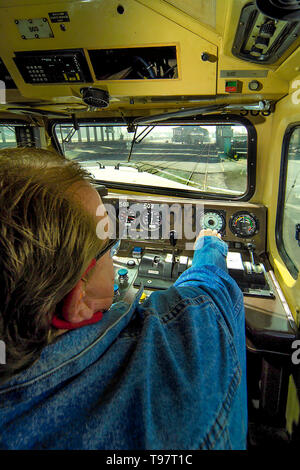 In the cab of his locomotive, a train engineer opens the throttle to leave a Los Angeles railroad yard. - Stock Photo