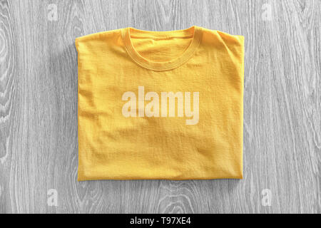 Blank yellow t-shirt on wooden background - Stock Photo