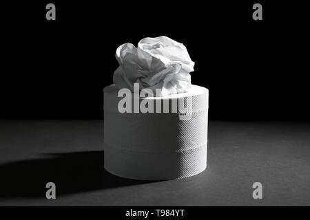 Roll of toilet paper on dark background - Stock Photo