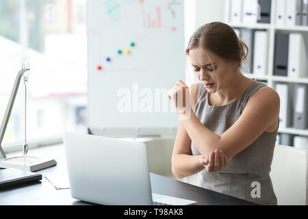 Young woman suffering from pain in elbow at workplace - Stock Photo