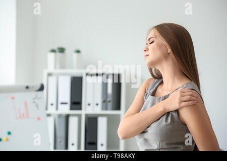 Young woman suffering from pain in shoulder at workplace - Stock Photo
