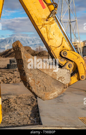 The dirty bucket and yellow arm of an excavator at a construction site - Stock Photo