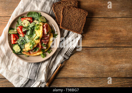 Tasty omelet with bacon and vegetables on plate - Stock Photo