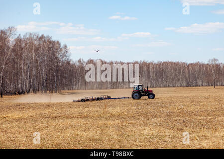 Red tractor with a trailed plow for mowing and weeding fields for the agro-industry of yellow color under the blue sky, a clear spring day. Preparatio