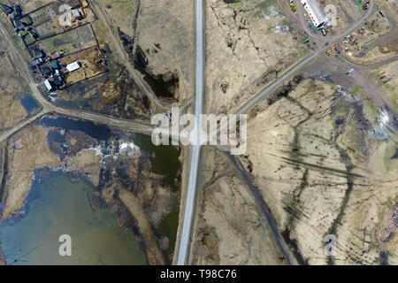 Aerial view of the intersection of asphalt and ground roads in the field far from the big cities on a clear spring day. Road junction in the desert ne - Stock Photo