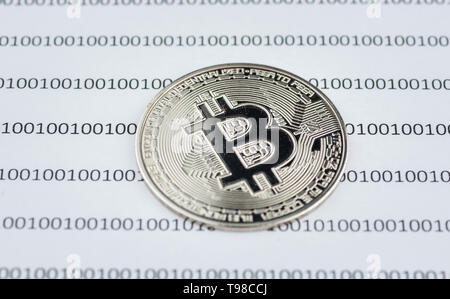 Bitcoin, cryptocurrency physical coin on paper with binary system of zeros and ones.Virtual cryptocurrency concept.Concept image for cryptocurrency - Stock Photo