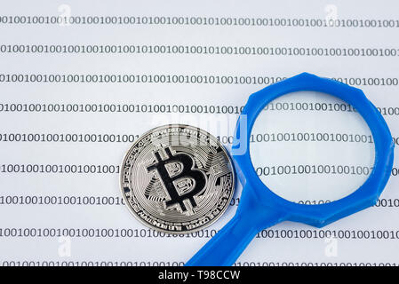 Magnifying glass over bitcoin, cryptocurrency physical coin on paper with binary system of zeros and ones.Virtual cryptocurrency concept.Concept image - Stock Photo