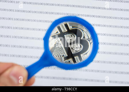Man hand holds magnifying glass over bitcoin, cryptocurrency physical coin on paper with binary system of zeros and ones.Virtual cryptocurrency concep - Stock Photo