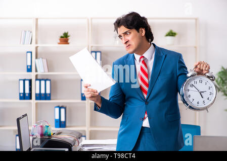 Young employee making copies at copying machine - Stock Photo