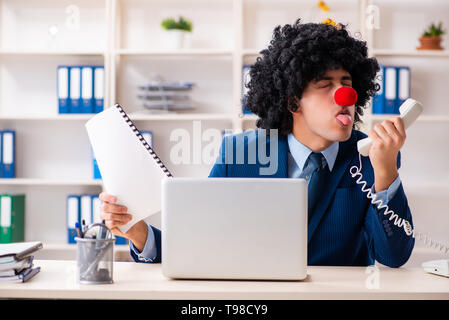 Young clown businessman working in the office - Stock Photo