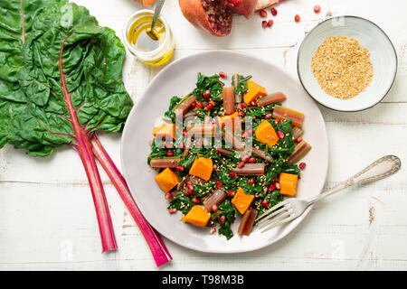 Boiled swiss chard with sweet potato, pomegranate and sesame seeds on a white wooden background. Top view - Stock Photo