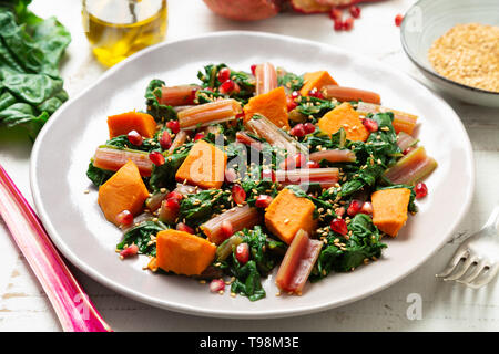 Boiled swiss chard with sweet potato, pomegranate and sesame seeds on a white wooden background - Stock Photo