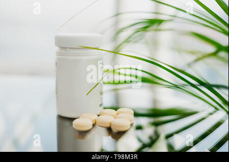 Plastic bottle with scattered light pills on a glass table, on a natural background and on a background of green leaves. - Stock Photo