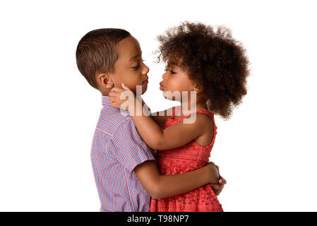 Two cheerful african-american siblings, sister kissing her brother, isolated on white background - Stock Photo