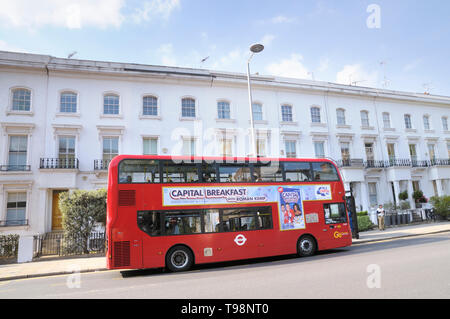 A red double-decker bus with an advertisement for Capital Radio, Chelsea, London, England, UK - Stock Photo