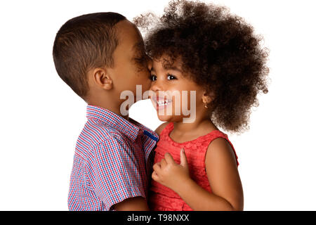 Two cheerful african-american siblings, brother kissing his sister, isolated on white background - Stock Photo