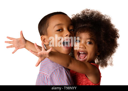 Two cheerful african-american siblings, sister hugging her brother, isolated on white background - Stock Photo