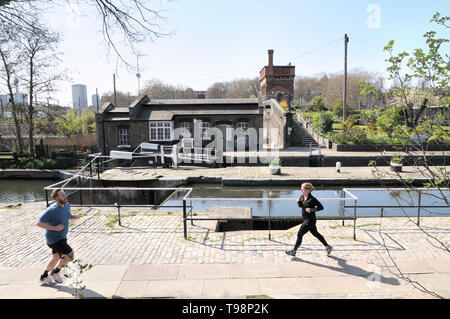 People jogging by St Pancras Lock with Lock Keepers Cottage and Waterpoint in the background, Regent's Canal, King's Cross, London, England, UK - Stock Photo