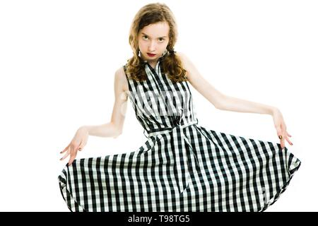 Teen girl in black checkered dress and dark make up posing on white background - Stock Photo