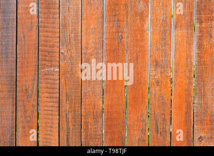 The aged old gray wooden fence is painted with orange paint, close-up - Stock Photo