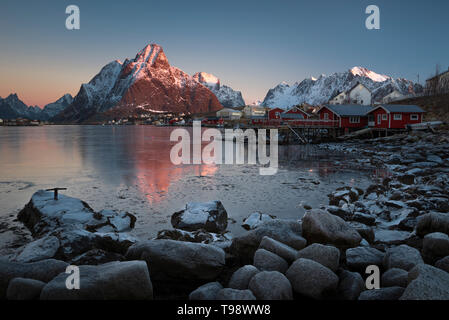 Morning light illuminates the snow-covered Olstinden in the fishing village Reine, Reine, Nordland, Norway - Stock Photo