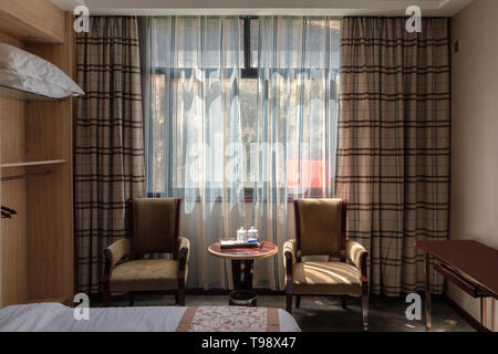 Chengdu, China - Oct 21 2018 : Interior sunlight through window with curtain in wooden brown bedroom with chairs and table - Stock Photo