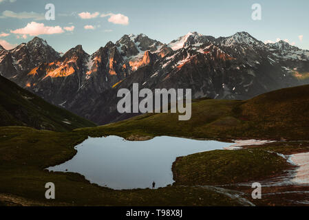 Hikers at Koruldi Lakes look out on the mountains of the Great Caucasus in the evening light, Upper Svanetia, Georgia - Stock Photo