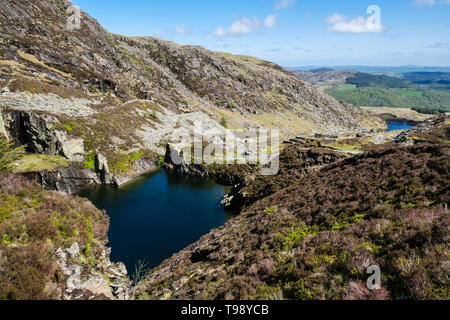 Flooded disused slate quarry pit and slag heaps on path route to Carnedd Moel Siabod mountain in Snowdonia National Park. Capel Curig Conwy Wales UK - Stock Photo