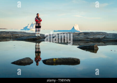 Inuit woman in traditional clothes stands on the shore of Disko Bay on Midsummer, Greenland