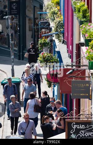 People walking along shops on historic Victoria Street in Edinburgh old town, Scotland, UK - Stock Photo
