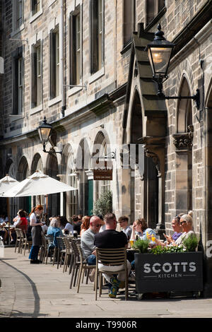 People drinking and eating in restaurants in sunny weather on Victoria Terrace above Victoria Street in Edinburgh Old Town, Scotland, UK - Stock Photo