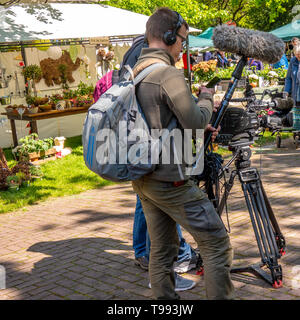 Hannover, Germany, May 12., 2019: Television crew of a local television station with a photographer and a sound engineer operating an old black video  - Stock Photo