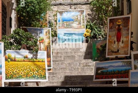 Paintings on display in the Corsa Umberto, Taormina, Sicily. - Stock Photo