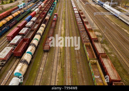 Aerial view of colorful freight trains with goods on the railway station. Top view from flying drone - Stock Photo